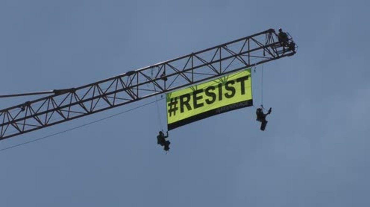 Belgium: Greenpeace activists scale crane near US embassy during Trump visit