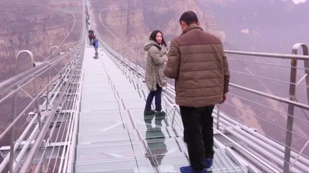 World's longest glass-bottomed bridge WOBBLES at 218 metres high