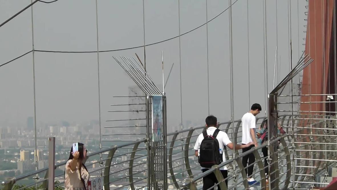 ¡No mires hacia abajo!  Turistas se enfrentan al puente de vidrio más largo del mundo en China
