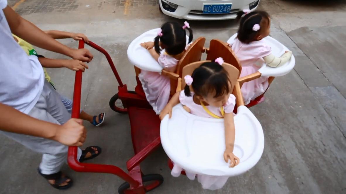 Este papá chino inventa un CARRITO GIRATORIO para sus hijas trillizas