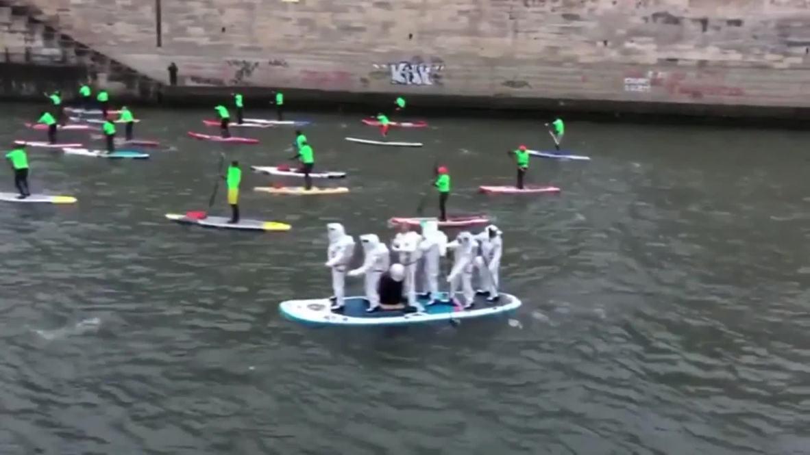 Cientos de aficionados del paddle surf participan en una carrera por el río Sena