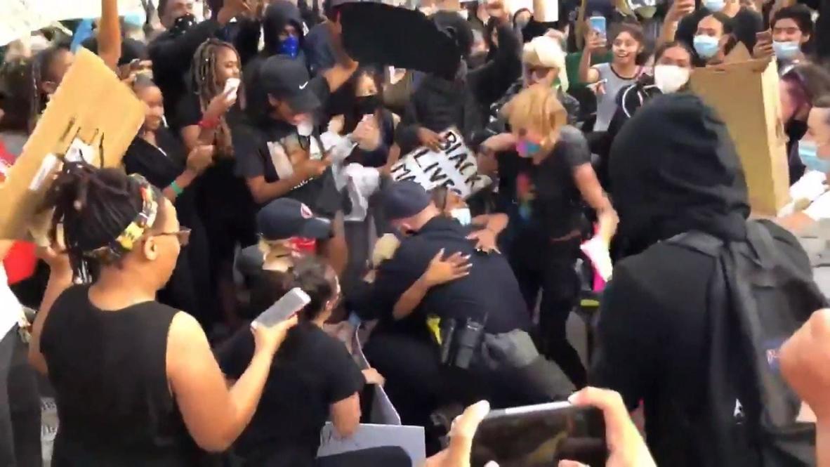EE.UU.: Agente de policía se arrodilla para abrazar a un manifestante en una protesta en California