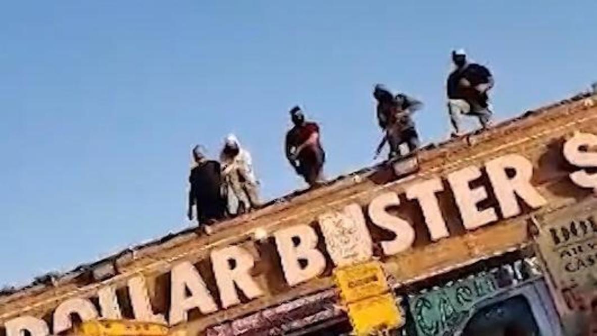 США: Вооруженные работники винного магазина стоят на страже на крыше, чтобы отпугнуть мародеров