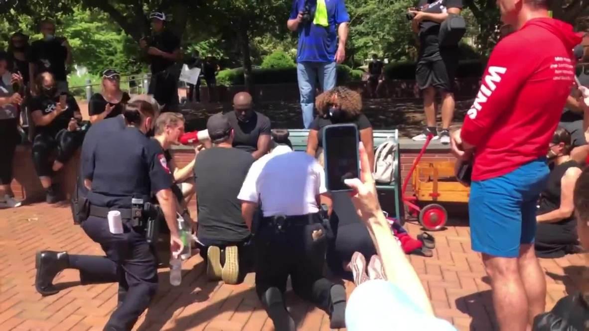الولايات المتحدة الأمريكية: عناصر شرطة من البيض يغسلون أقدام رجال دين من ذوي البشرة السمراء خلال صلاة على روح فلويد
