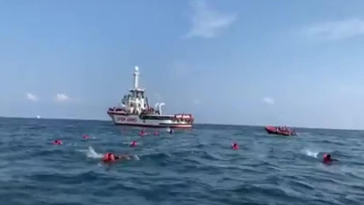 Italia: Migrantes saltan por la borda del 'Open Arms' para nadar hasta la costa de Sicilia