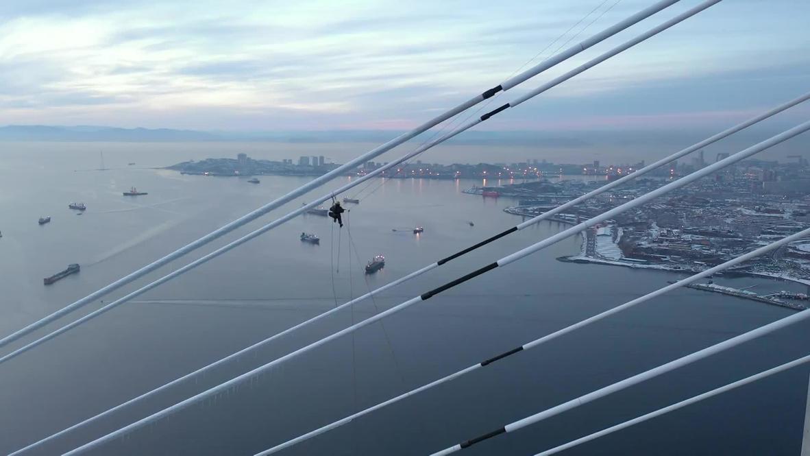 روسيا: صور جوية لأعمال تنظيف كابلات جسر روسكي الشاهق من الجليد بعد هطول أمطار متجمدة