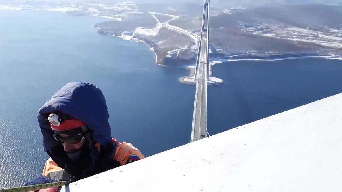 Россия: Спасатели МЧС очищают мост Русский на высоте 300 метров