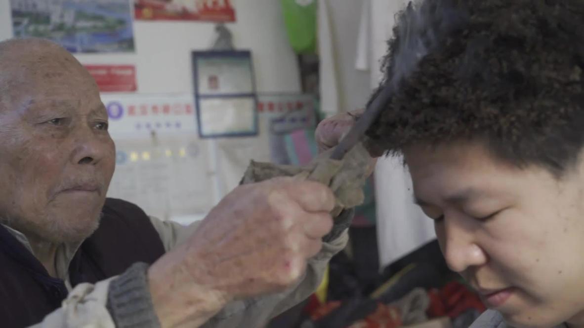 Un barbero chino de 91 años utiliza una barra de hierro caliente para cortar el pelo
